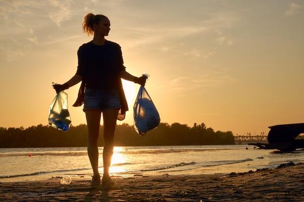 검은 장갑에 어린 소녀가 강의 더러운 해변을 따라 쓰레기 봉투와 함께 걷고 있습니다.