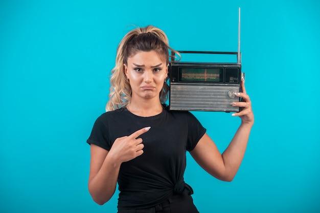 Молодая девушка в черной рубашке держит на плече старинное радио и колеблется.