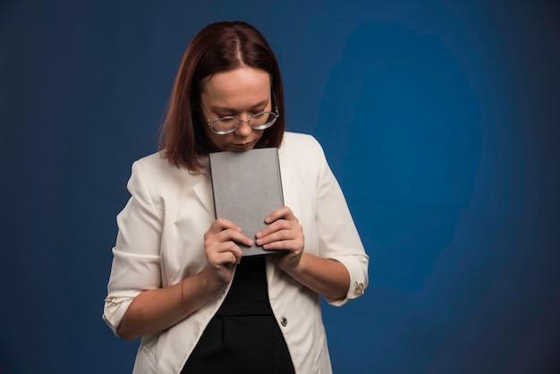 Молодая девушка в черной рубашке кладет книгу под подбородок.