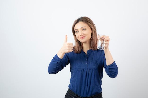 水を保持し、親指をあきらめる青いブラウスの少女。