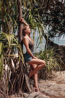 Молодая девушка в синих джинсах возле тропических пальм