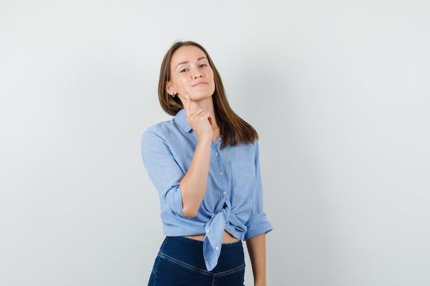 Молодая девушка в синей рубашке, штанах держит палец на подбородке и выглядит уверенно