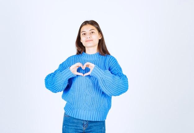 Молодая девушка в синем свитере показывает сердце двумя руками.