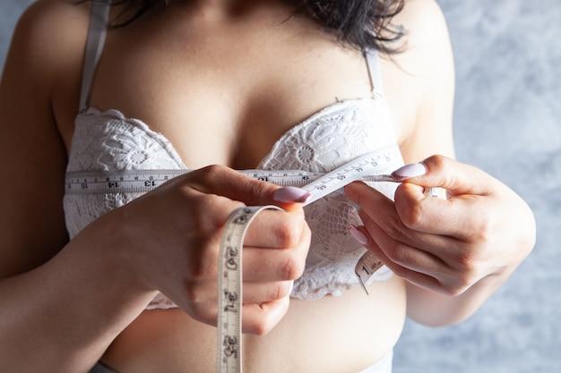 Молодая девушка в бюстгальтерах измеряет грудь