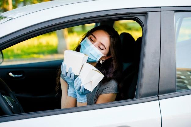 의료 장갑과 마스크에 차에 어린 소녀 상자에 냄비를 보유