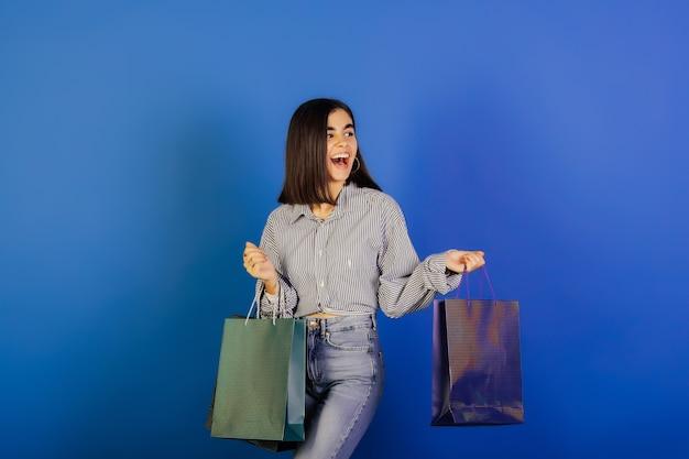 Молодая девушка в повседневной одежде, голубой рубашке и джинсах, держа хозяйственные сумки на голубой поверхности.
