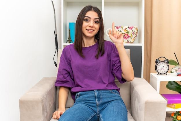 Молодая девушка в повседневной одежде счастлива и позитивно показывает указательный палец с новой хорошей идеей, сидя на стуле в светлой гостиной