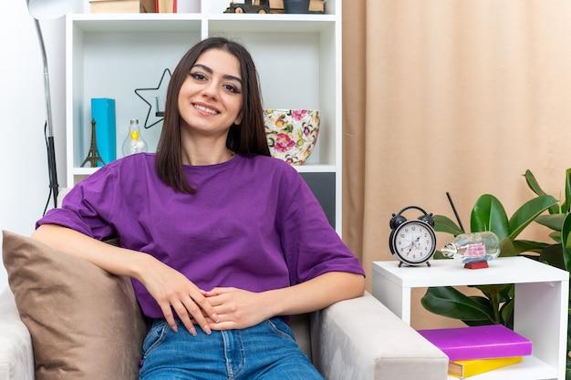 행복하고 긍정적 인 캐주얼 옷을 입은 어린 소녀가 밝은 거실의 자에 유쾌하게 앉아 웃고 있습니다.