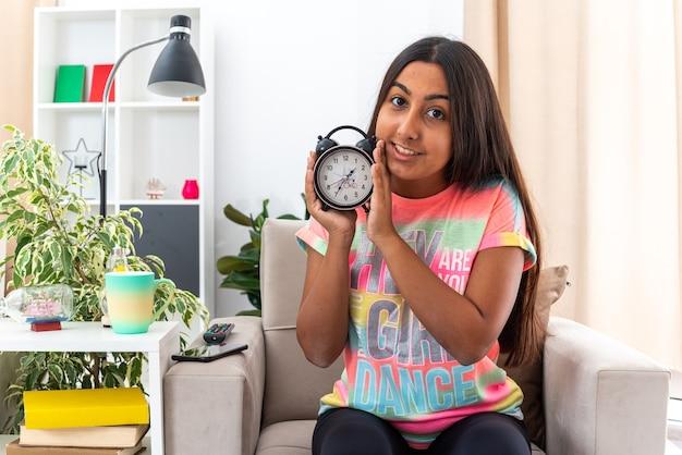 Молодая девушка в повседневной одежде с будильником выглядит счастливой и позитивной, весело улыбаясь, сидя на стуле в светлой гостиной