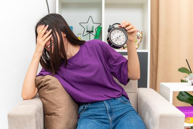 Молодая девушка в повседневной одежде держит будильник, весело улыбаясь, прикрывая лицо ладонью, сидя на стуле в светлой гостиной
