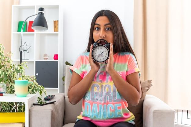 Молодая девушка в повседневной одежде держит будильник с удивлением, сидя на стуле в светлой гостиной
