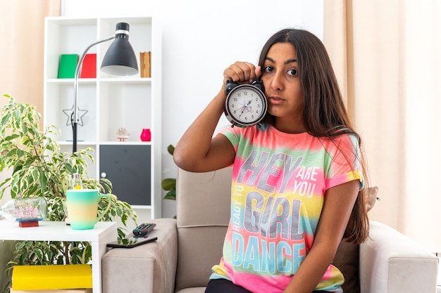 Молодая девушка в повседневной одежде держит будильник, выглядя обеспокоенными и смущенными часами, сидя на стуле в светлой гостиной