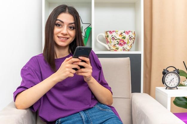 Молодая девушка в повседневной одежде, держащая смартфон, смотрит с улыбкой на лице, счастливая и позитивная, сидя на стуле в светлой гостиной