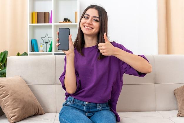 Молодая девушка в повседневной одежде держит смартфон, весело улыбаясь, показывает палец вверх, сидя на диване в светлой гостиной