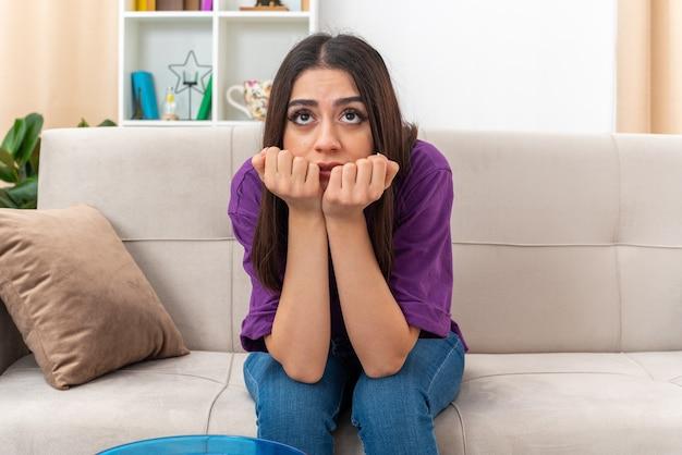 Молодая девушка в повседневной одежде, глядя в сторону с руками на подбородке, подавленная с грустным выражением лица, сидит на диване в светлой гостиной