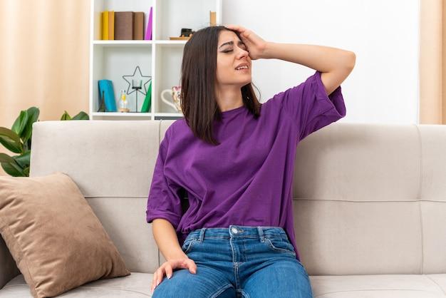 Молодая девушка в повседневной одежде выглядит уставшей и скучающей, положив руку на голову, сидя на диване в светлой гостиной