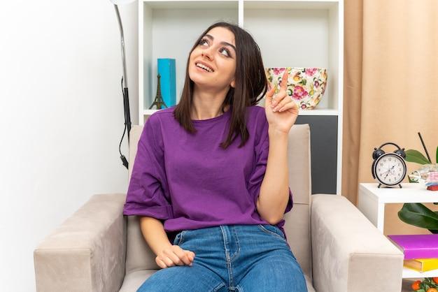 Молодая девушка в повседневной одежде смотрит вверх с улыбкой на лице, счастливая и веселая, показывая указательный палец, сидя на стуле в светлой гостиной