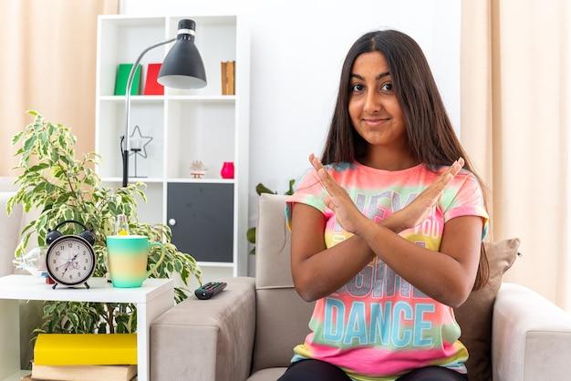 明るいリビング ルームの椅子に座って手を交差させる停止ジェスチャーを作る顔に笑顔で見ているカジュアルな服の若い女の子