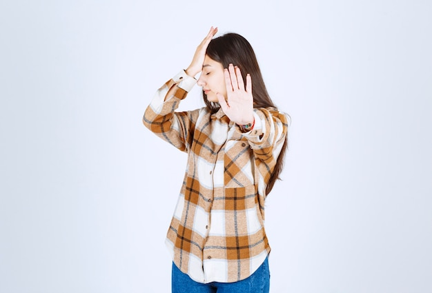 立って、白い壁に一時停止の標識を与えるカジュアルな服を着た少女。