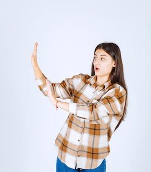 평상복을 입은 어린 소녀가 서서 흰 벽에 정지 신호를 줍니다.