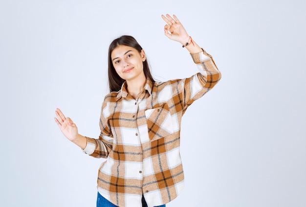 Молодая девушка в повседневной одежде стоя и позирует на белой стене.