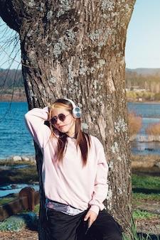 Молодая девушка в повседневной одежде, используя ее наушники и мобильный телефон, чтобы слушать музыку.