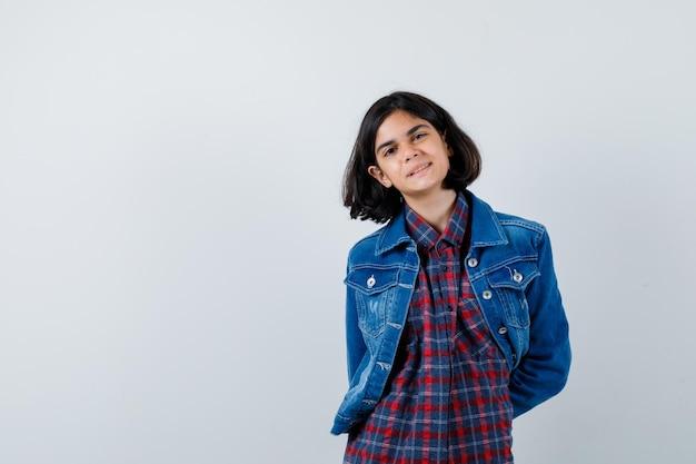 チェックシャツとジーンズのジャケットを着た少女が腰の後ろで手をつないで、かわいく見える、正面図。