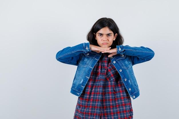 チェックシャツとジージャンの少女が手の下にあごをもたれ、真剣に見える、正面図。