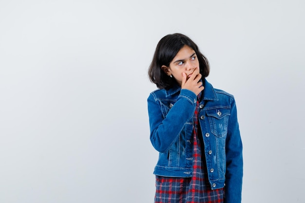 チェックシャツとジーンズのジャケットを着た少女が目をそらし、カメラに向かってポーズをとって物思いにふける、正面図。