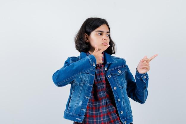 검지 손가락으로 오른쪽을 가리키고 진지하게 보이는 체크 셔츠와 진 재킷을 입은 어린 소녀