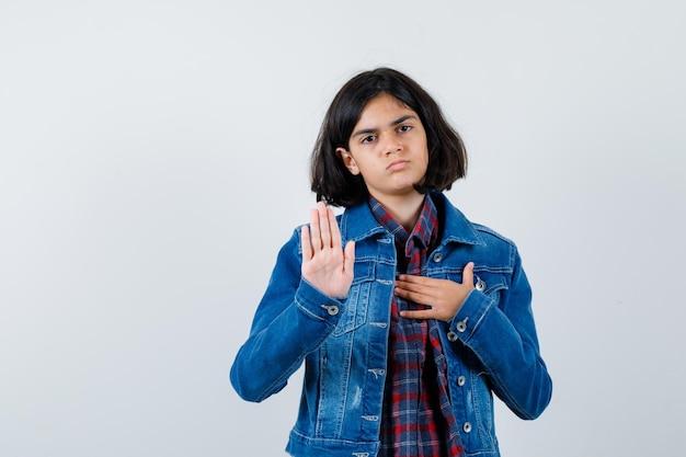 Молодая девушка в клетчатой рубашке и джинсовой куртке показывает знак остановки, положив руку на грудь и выглядит серьезно