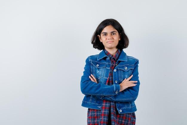 チェックシャツとジージャンの立っている腕を組んで幸せそうに見える若い女の子、正面図。