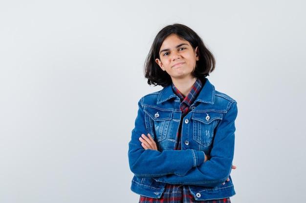 체크 셔츠와 진 재킷을 입은 어린 소녀가 팔짱을 끼고 예쁜 앞모습을 보고 있습니다.