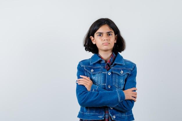 체크 셔츠와 진 재킷을 입은 어린 소녀가 팔짱을 끼고 진지한 정면을 바라보고 있습니다.