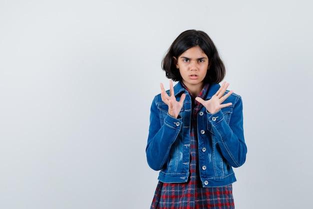 Молодая девушка в клетчатой рубашке и джинсовой куртке протягивает руки, как держит что-то и выглядит испуганной, вид спереди.