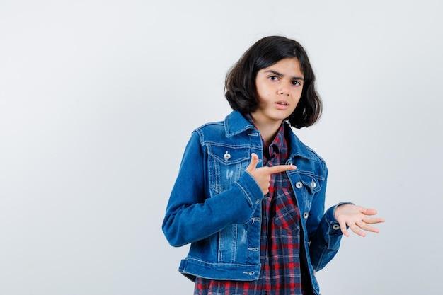 체크 셔츠와 진 재킷을 입은 어린 소녀가 한 손으로 무언가를 잡고 검지 손가락으로 가리키며 진지한 모습으로 앞을 바라보고 있습니다.