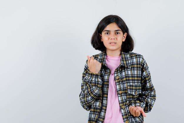 チェックシャツとピンクのtシャツの若い女の子が拳を握りしめ、きれいに見える、正面図。