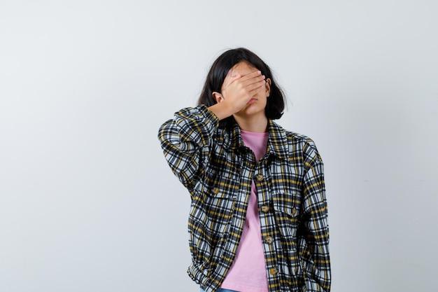 チェックシャツとピンクのtシャツの少女が手で目を覆い、臆病な正面図を探しています。
