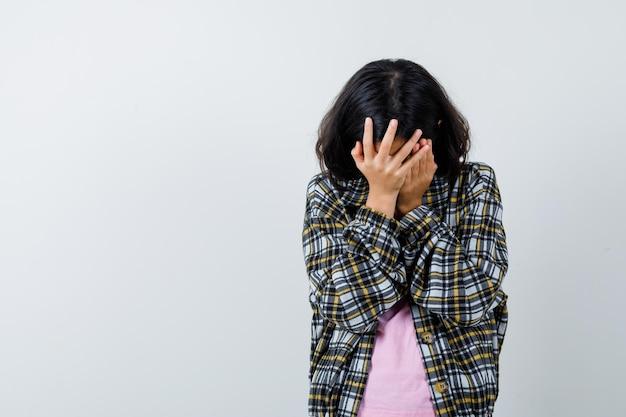 Молодая девушка в клетчатой рубашке и розовой футболке закрыла лицо руками и выглядела раздраженной, вид спереди.