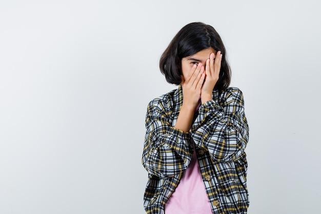 Молодая девушка в клетчатой рубашке и розовой футболке закрывает лицо руками и выглядит робко