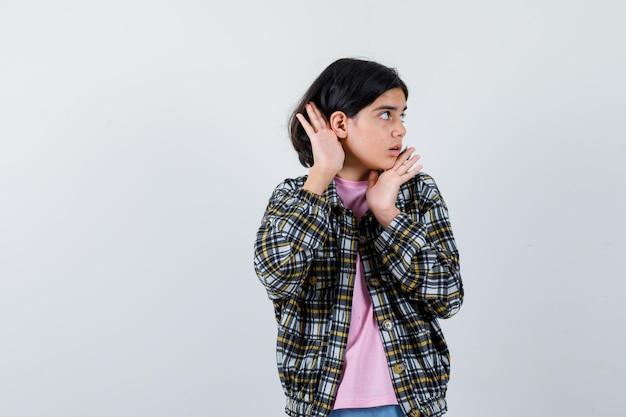 체크 셔츠와 핑크색 티셔츠를 입은 어린 소녀가 귀 근처에 손을 잡고 무언가를 듣고 집중하고 있는 앞모습을 보고 있습니다.