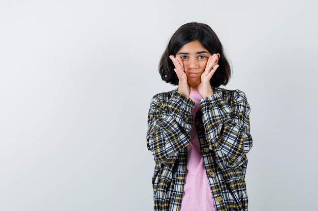 Молодая девушка в клетчатой рубашке и розовой футболке, взявшись за руки на лице и робко глядя, вид спереди.