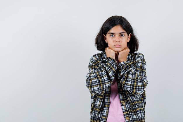 チェックシャツとピンクのtシャツの若い女の子は拳に顎をもたれ、真剣に見える、正面図。