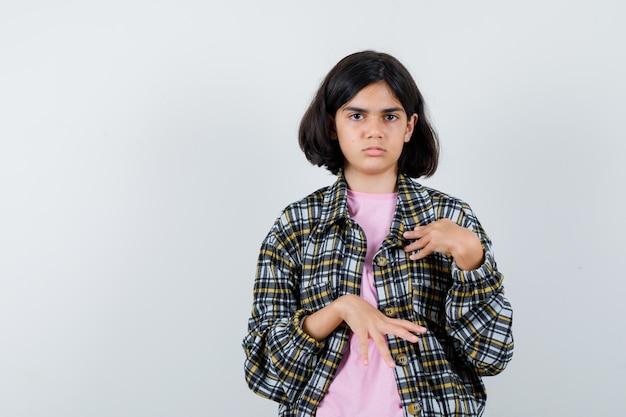 チェックシャツとピンクのtシャツを着た少女が手で自分を指して真剣に見える