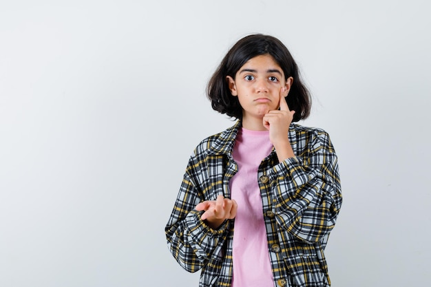 チェックシャツとピンクのtシャツの若い女の子は、目の領域に人差し指を置き、拳を握りしめ、きれいに見える、正面図。