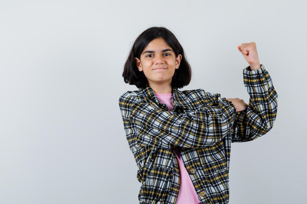 Молодая девушка в клетчатой рубашке и розовой футболке демонстрирует мощный жест и выглядит мощно, вид спереди.