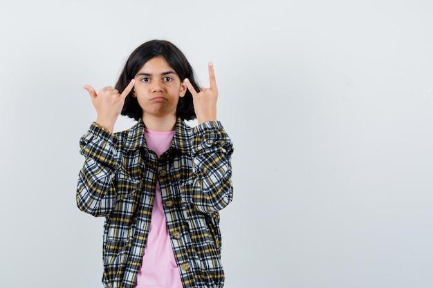 Молодая девушка в клетчатой рубашке и розовой футболке показывает жест рок-н-ролла и мизинец и выглядит серьезной, вид спереди.