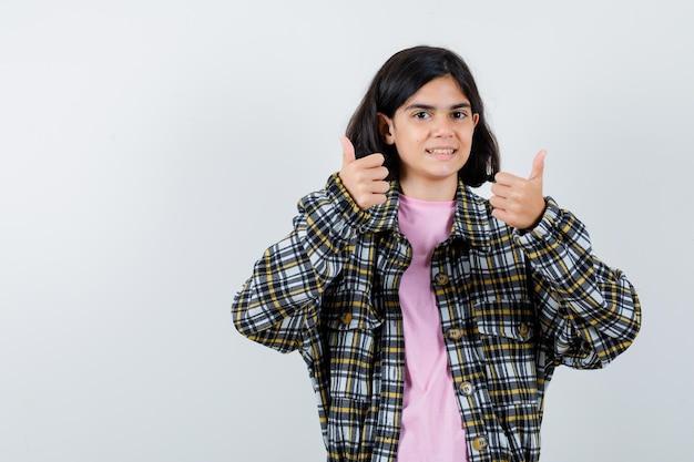 チェックシャツとピンクのtシャツを着た少女が両手で親指を立てて幸せそうに見える正面図。
