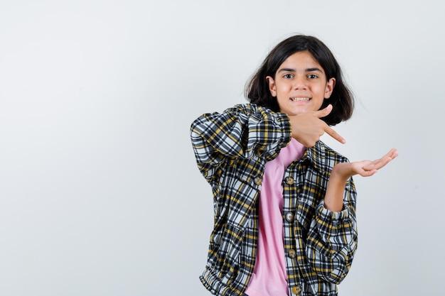 체크 셔츠와 분홍색 티셔츠를 입은 어린 소녀가 한 손으로 무언가를 잡고 검지 손가락으로 가리키고 앞모습이 예뻐 보입니다.