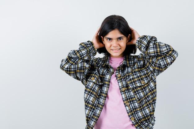 チェックシャツとピンクのtシャツの若い女の子が両手で髪を押し込んで、きれいに見える、正面図。